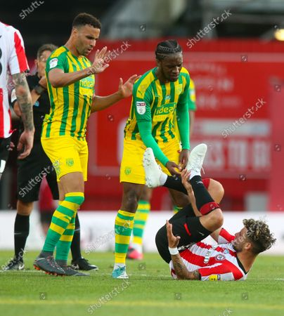 Emiliano Marcondes of Brentford (floor) tangles with Jake Livermore of West Bromwich Albion (L) & Romaine Sawyers of West Bromwich Albion