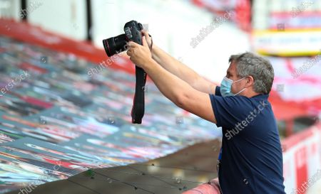 Photographer takes pictures of the Supporters' faces on a banner on the terrace