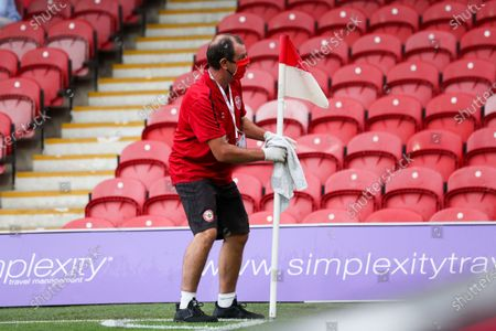 Ground staff sanitise the corner flag and goalpost pre-match