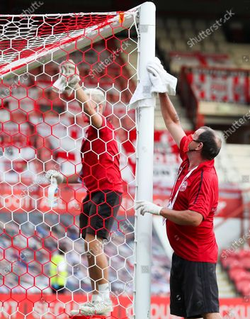 Ground staff sanitise the corner flag and goalposts pre-match