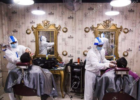 Barbers dressed in protective suits and face masks trim hair as businesses reopen in Dhaka, Bangladesh. The country's government has announced that certain businesses including large shops, malls and hair salons could reopen to restart the economy, following the COVID-19 outbreak