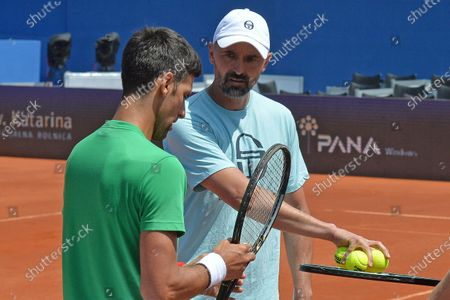 Stock Photo of Former Wimbledon champion Goran Ivanisevic, left, who now coaches top-ranked Novak Djokovic, right, attends a training session during an exhibition tournament in Zadar, Croatia. The Croatian great, who won his only Grand Slam title at the All England Club in 2001, wrote on Instagram that he tested positive for coronavirus after two negative tests in the last 10 days