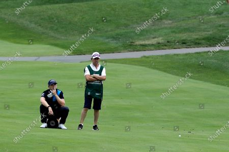 Stock Image of Matt Wallace, left, of England, waits to play his ball on the 13th fairway next to his caddie David McNeilly during the second round of the Travelers Championship golf tournament at TPC River Highlands, in Cromwell, Conn. Wallace is playing the second round by himself after two other golfers in his group, Denny McCarthy and Bud Cauley, withdrew from the tournament. McCarthy told Golfchannel.com that he withdrew from the tournament after feeling sick Thursday night and testing positive for the coronavirus on Friday. Cauley, who played with McCarthy on Thursday, also withdrew before Friday's second round. McCarthy became the third PGA Tour player to test positive for the virus since its restart and the second this week, joining Cameron Champ who withdrew on Tuesday. Nick Watney withdrew just before the second round of last week's RBC Heritage Championship