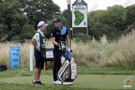 Matt Wallace, right, of England, stands with his caddie David McNeilly before teeing off on the third hole during the second round of the Travelers Championship golf tournament at TPC River Highlands, in Cromwell, Conn. Wallace is playing the second round by himself after two other golfers in his group, Denny McCarthy and Bud Cauley, withdrew from the tournament. McCarthy told Golfchannel.com that he withdrew from the tournament after feeling sick Thursday night and testing positive for the coronavirus on Friday. Cauley, who played with McCarthy on Thursday, also withdrew before Friday's second round. McCarthy became the third PGA Tour player to test positive for the virus since its restart and the second this week, joining Cameron Champ who withdrew on Tuesday. Nick Watney withdrew just before the second round of last week's RBC Heritage Championship