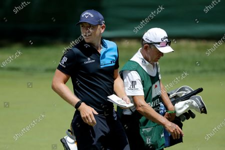 Matt Wallace, left, of England, walks with his caddie David McNeilly to the fourth tee box during the second round of the Travelers Championship golf tournament at TPC River Highlands, in Cromwell, Conn. Wallace is playing the second round by himself after two other golfers in his group, Denny McCarthy and Bud Cauley, withdrew from the tournament. McCarthy told Golfchannel.com that he withdrew from the tournament after feeling sick Thursday night and testing positive for the coronavirus on Friday. Cauley, who played with McCarthy on Thursday, also withdrew before Friday's second round. McCarthy became the third PGA Tour player to test positive for the virus since its restart and the second this week, joining Cameron Champ who withdrew on Tuesday. Nick Watney withdrew just before the second round of last week's RBC Heritage Championship