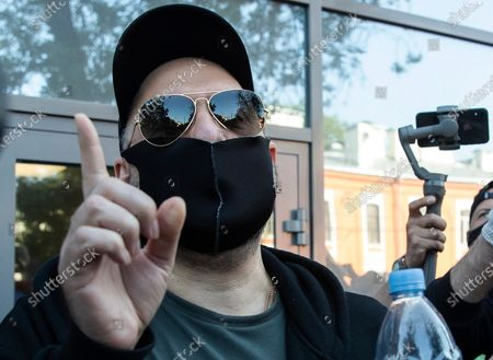 Russian film and theater director Kirill Serebrennikov, wearing a face mask to protect against coronavirus, gestures as he leaves the Meshchansky court after hearings in Moscow, Russia, . A Moscow judge convicted an acclaimed Russian theater director of embezzling state funds and imposed a three-year suspended sentence Friday in a case widely seen as politically motivated