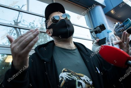 Russian film and theater director Kirill Serebrennikov, wearing a face mask to protect against coronavirus, speaks to media as he leaves the Meshchansky court after hearings in Moscow, Russia, . A Moscow judge convicted an acclaimed Russian theater director of embezzling state funds and imposed a three-year suspended sentence Friday in a case widely seen as politically motivated