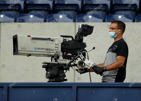 A TV Camera with a face mask on before the start of the match