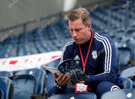 Cardiff City manager Neil Harris reads the match day programme before the start of the match