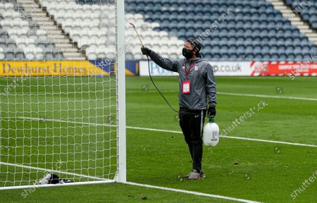 A groundsman disinfects the goal posts during the drinks break