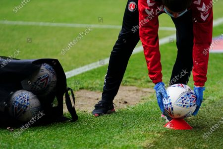 A member of ground staff wearing protective gloves places a ball on a cone during the match