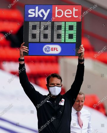 The fourth official wears a protective mask as he holds up the Sky Bet substitutes board