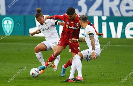 Aleksander Mitrovic of Fulham tussles with Kalvin Phillips and Ben White of Leeds United
