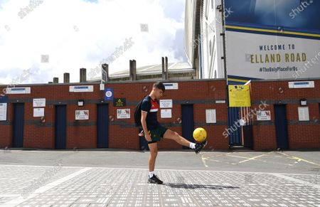 A boy plays football in front of the closed turnstiles at Elland Road before kick off