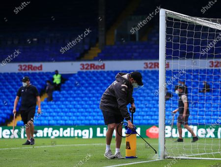 A member of the groundstaff sprays disinfectant onto the goal post