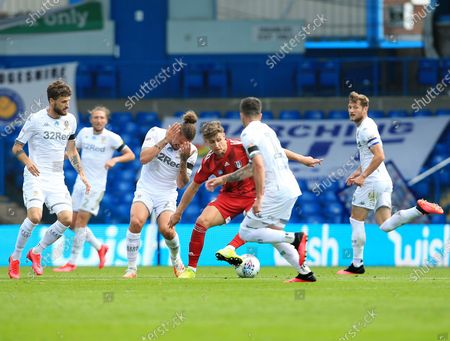 Tom Cairney of Fulham is surrounded by Leeds United players