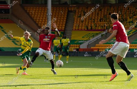 Todd Cantwell of Norwich City scores the equalising goal, 1-1, as Fred of Manchester United tries to block.