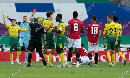 Referee Jonathan Moss shows a red card tp Timm Klose of Norwich City