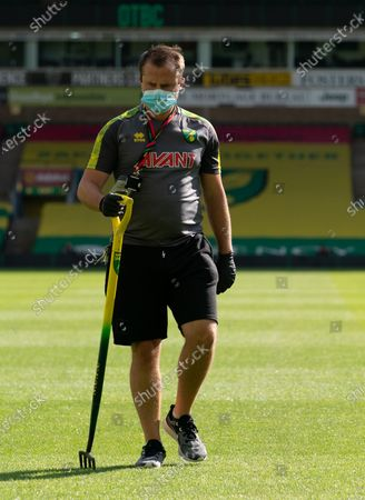 Norwich City staff wear PPE / Face Masks while tending to the pitch