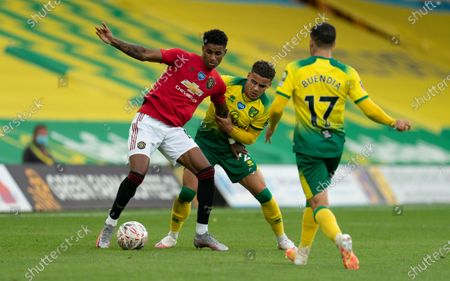 Marcus Rashford of Manchester United is surrounded by Max Aarons of Norwich City and Emiliano Buendia of Norwich City