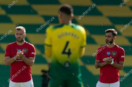 Luke Shaw of Manchester United and Bruno Fernandes of Manchester United stand for a minutes applause for the NHS