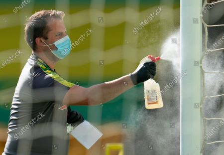 Norwich City staff wear PPE / Face Masks while disinfecting the goal posts