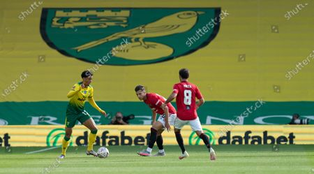 Jamal Lewis of Norwich City tries to run past Diogo Dalot of Manchester United and Juan Mata of Manchester United