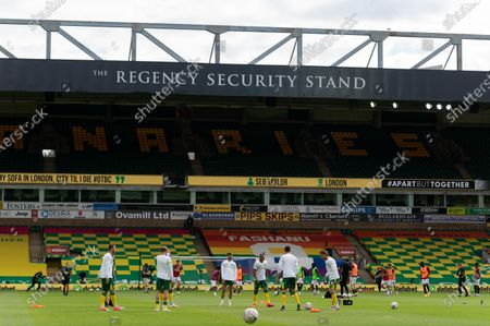 Norwich City oplayers warm-up with a back-drop of empty seats