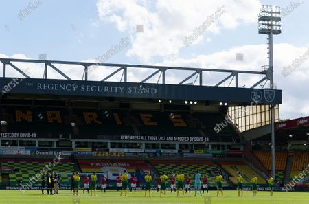Norwich City and Manchester United players stand for a minutes applause for the NHS