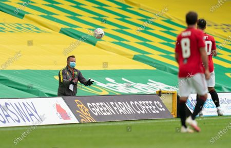 Norwich City staff wearing PPE / Face Mask returns the ball  to the field of play
