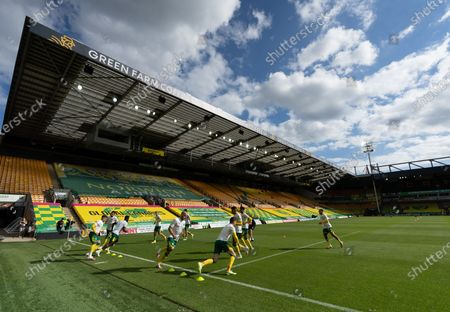 Norwich City players warms-up in front of an empty stand