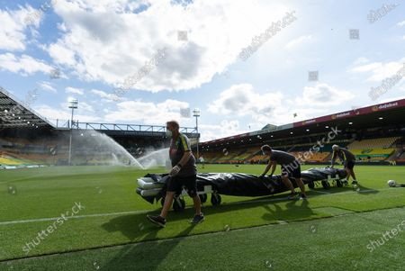 Norwich City staff remove the training goal while wearing PPE / Face Masks