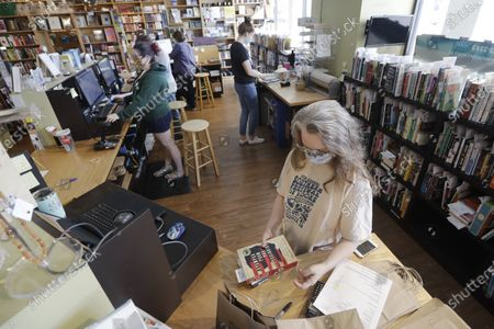 Workers fill customers' orders in Parnassus Books in Nashville, Tenn. The independent bookstore, owned by novelist Ann Patchett and Karen Hayes, opened and thrived while others were closing their doors and is once again defying the odds during the coronavirus pandemic