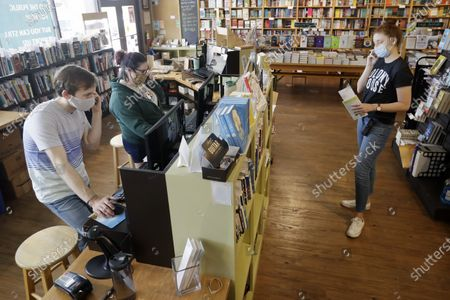 Employees help customers with their orders on the phone in Parnassus Books in Nashville, Tenn. The independent bookstore, owned by novelist Ann Patchett and Karen Hayes, opened and thrived while others were closing their doors and is once again defying the odds during the coronavirus pandemic