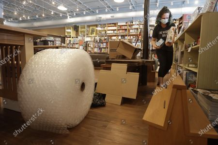 Shipping materials fill a section of the store as Cat Bock gathers items for a customer's order in Parnassus Books in Nashville, Tenn. The retail floor of the independent bookstore has essentially become a distribution center since it is closed to customers during the coronavirus pandemic