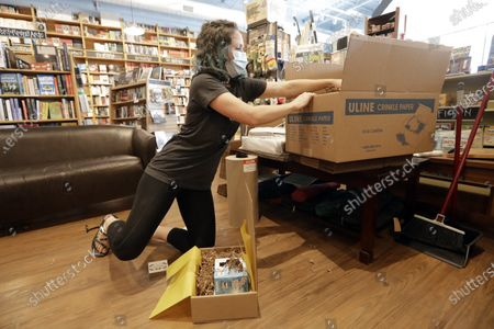 Stock Photo of Cat Bock packs items for shipping to a customer from Parnassus Books in Nashville, Tenn. The retail floor of the independent bookstore has essentially become a distribution center since it is closed to customers during the coronavirus pandemic