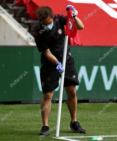 A groundsman cleans the corner flag with wipes before kick off.