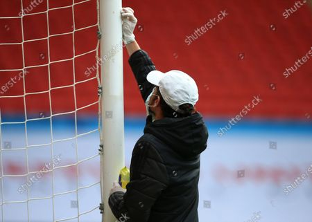 A member of groundstaff wipes down the goal post with disinfectant