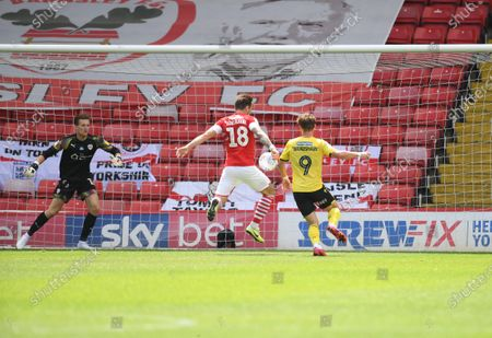 Barnsley's Michael Sollbauer knees the ball out of play.