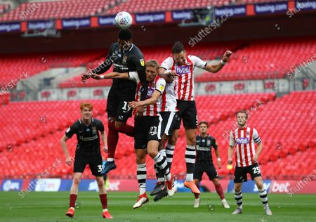 Vadaine Oliver of Northampton Town gets to a header above Dean Moxey of Exeter City