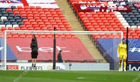 During a drinks break, Northampton goalkeeper Steve Arnold waits as the cross bar is wiped down according to the new corona virus regulations