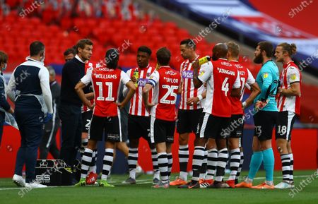 Exeter City manager Matt Taylor talks to his players during a drink break