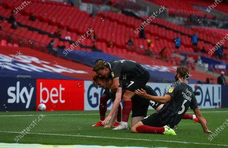 Callum Morton of Northampton Town, with Sam Hoskins and Jordan Turnbull, celebrate scoring the second goal during the League 2 Play Off final