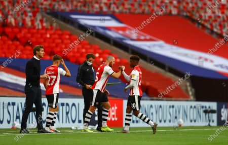 Exeter City manager Matt Taylor urges on his players during the match between Exeter City and Northampton Town for the League 2 Play Off Final as his substitutes touch elbows