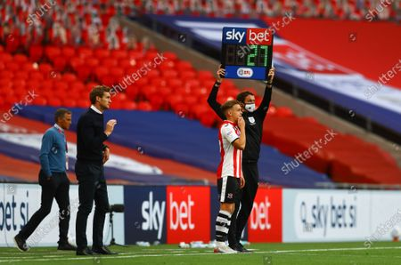 Exeter City manager Matt Taylor stands near The Sky Bet EFL substitutes board held up by the fourth official Leigh Doughty during the match between Exeter City and Northampton Town for the League 2 Play Off Final