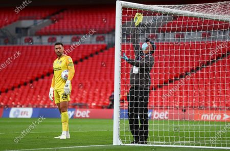 During a drinks break, Northampton goalkeeper Steve Arnold waits as the cross bar is wiped down according to the new corona virus match regulations