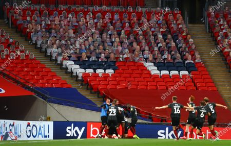 Sam Hoskins of Northampton Town and his team mates celebrates scoring the third goal, in front of Sky Bet and Carabao branding and many Northampton fan's cardboard cut outs inside an empty Wembley Stadium during the League 2 Play Off final