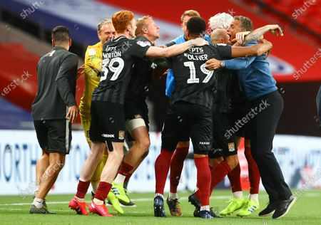 Northampton Town manager Keith Curle and the rest of the squad celebrate at full-time as his side secure promotion to League One, during the Sky Bet League Two Play off Final between Exeter City and Northampton Town