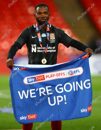 Mark Marshall of Northampton Town stands with a 'We're Going Up' flag after his team beat Exeter City 4-0 in the Sky Bet Play off Final and securing promotion to League One.