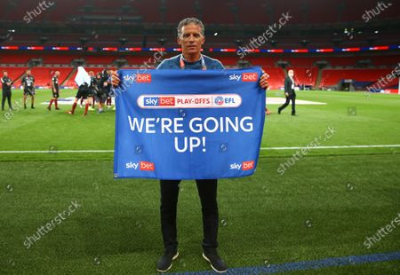 Northampton Town manager Keith Curle stands with a 'We're Going Up' flag after his team beat Exeter City 4-0 in the Sky Bet Play off Final and securing promotion to League One.